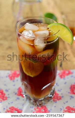 Rum and Coke Cocktail Drink with Lime Wedges on The Rocks