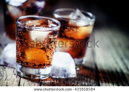 Rum and cola and ice, dark wood background, selective focus, shallow depth of field - stock photo