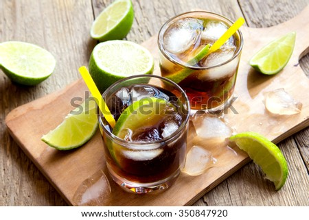 Rum and cola Cuba Libre drink with lime and ice on rustic wooden table - stock photo