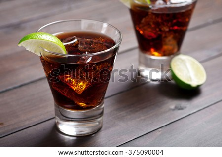 Rum and Cola Cuba Libre with Lime and Ice on wooden table closeup - stock photo