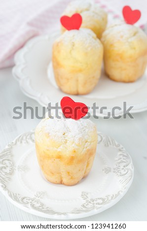 Rum Baba decorated with red hearts on the plate and a few more in the background