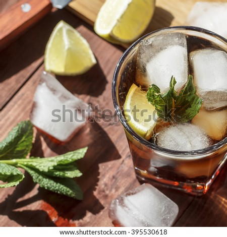 rum cocktail in a glass with ice, lime, mint, bread on a wooden table. luxury brandy, cuba libre. Square shot. - stock photo