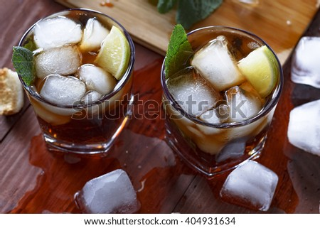 RUM , coctail cuba libra, rum and cola cuba libre with lime and Ice into the glass beaker closeup - stock photo