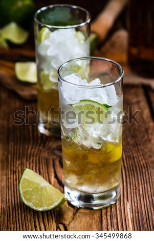 Rum on the rocks (for a Cuba Libre longdrink)  on wooden background