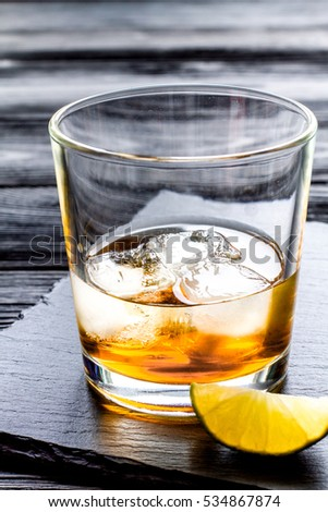 rum with ice in glass on dark background and lime