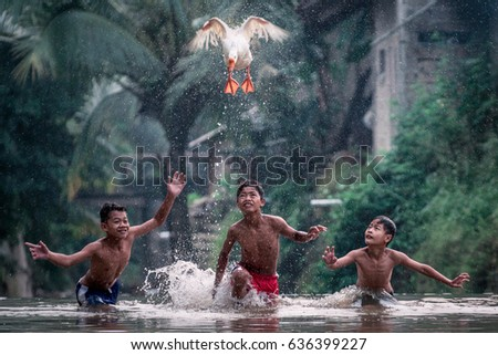 Rumpin, Bogor, Indonesia - April 16, 2017 : Boys playing with a goose in the river