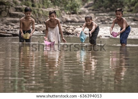 Rumpin, Bogor, Indonesia - April 16, 2017 : Village kids playing with boats made from paper