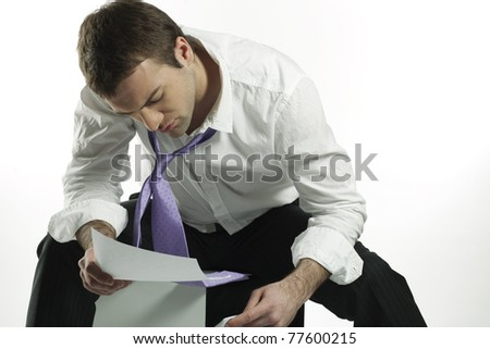 rumpled businessman looking at reports in dismay - stock photo