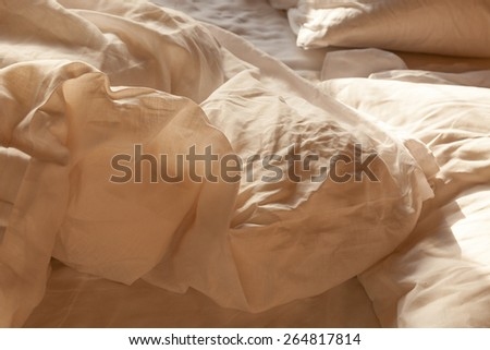 Rumpled unmade bed with linen duvet, sheets and pillows. Selective focus with shallow depth of field.  Background concept for romance. - stock photo