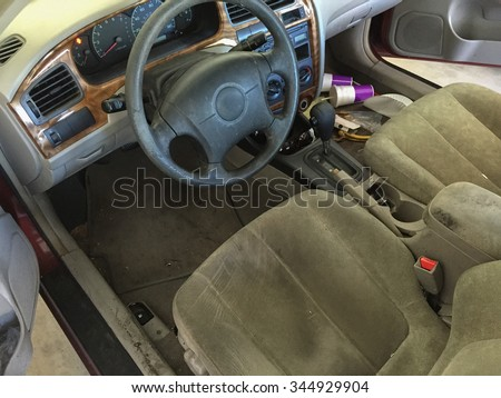 Run Down Car Interior, car cabin cluttered with fast food cups and trash showing run down fabric and faux leather trim on steering wheel and dirty dashboard console - stock photo