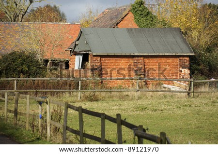 run down derelict farm in the middle of farmland and fields - stock photo