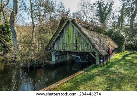 Run down thatched boathouse, in need of repair, on Norfolk Broads surrounded by trees - stock photo