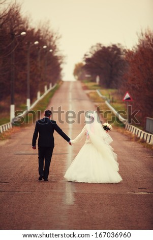 Runaway bride and groom - stock photo