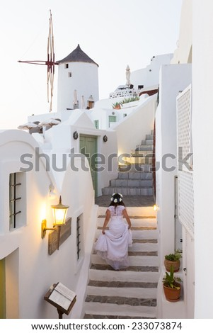 Runaway bride ona a staircase among traditional whitewashed  houses of Oia village on Santorini island, Greece. - stock photo