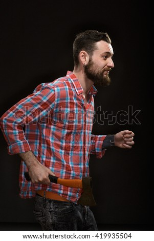 Runaway. Stylish bearded hipster guy walking with an axe on black background at the studio.