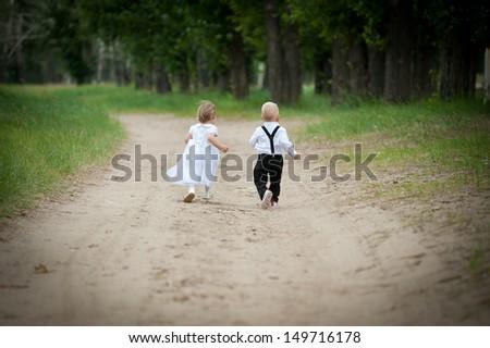 runaway two babies (boy and girl) run on road - stock photo