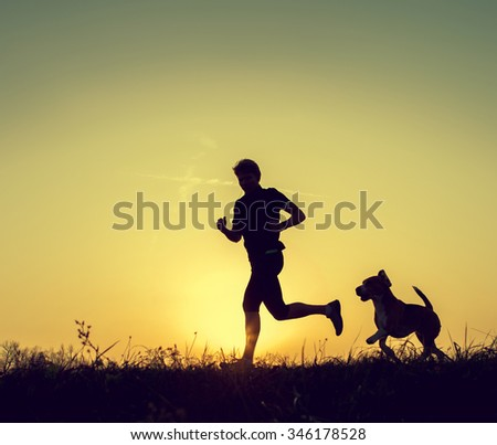 Runner and his dog sunset silhouettes - stock photo