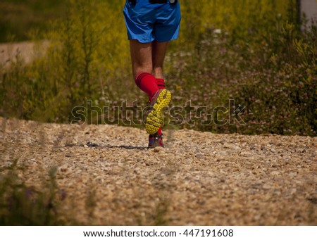 Runner athlete feet running on off-road surface.