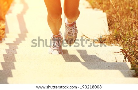 Runner athlete legs running on mountain stone stairs. woman fitness jogging workout wellness concept.  - stock photo