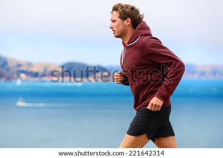 Runner athlete man running in sweatshirt hoodie in autumn fall by the water. Male runner training outdoors jogging in nature. - stock photo