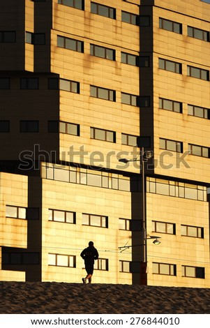 runner athlete man silhouette in the beach city with buildings at sunset in Corunna Spain - stock photo