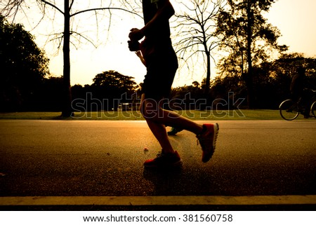 Runner athlete running at garden. man/woman fitness silhouette sunrise jogging workout wellness concept.- Warm tone and sun light. - stock photo