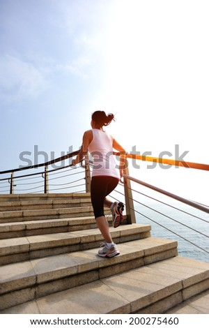 Runner athlete running at seaside stone stairs. woman fitness  jogging workout wellness concept.  - stock photo