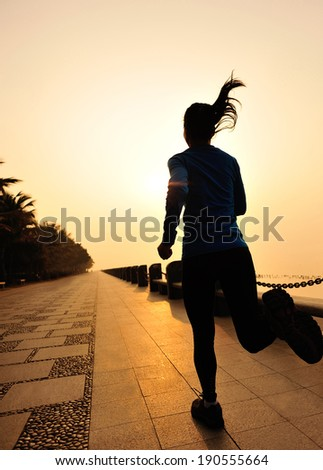 Runner athlete running at seaside woman fitness jogging silhouette sunrise workout wellness concept.  - stock photo