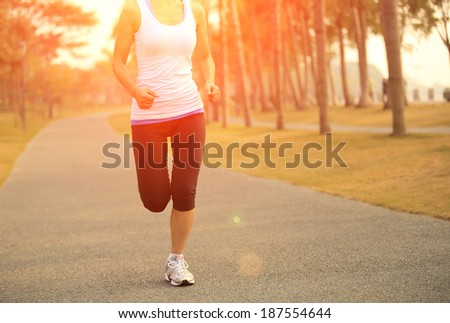Runner athlete running at tropical park.woman fitness jogging workout wellness concept.