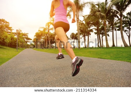 Runner athlete running at tropical park. woman fitness sunrise jogging workout wellness concept.  - stock photo