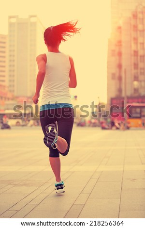 Runner athlete running on city street. woman fitness jogging workout wellness concept.  - stock photo