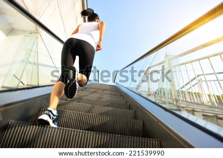Runner athlete running on escalator stairs. woman fitness jogging workout wellness concept.  - stock photo