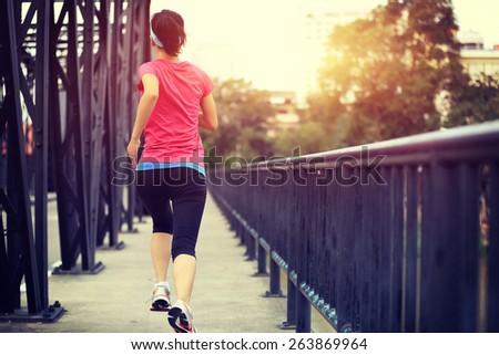 Runner athlete running on iron bridge. woman fitness jogging workout wellness concept.  - stock photo