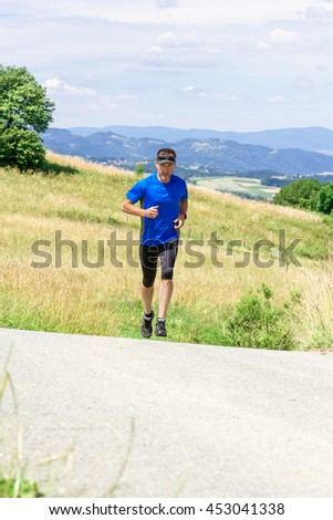 Runner athlete running on road at mountains background