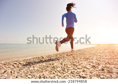 Runner athlete running on stone beach of qinghai lake. woman fitness jogging workout wellness concept.  - stock photo