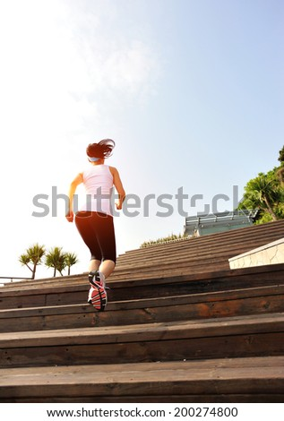 Runner athlete running up on wooden deck. woman fitness sunrise jogging workout wellness concept.