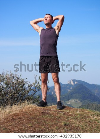 Runner athlete standing on summit of mountain, sunbathing and relaxing. Summer, Pieniny, Poland. - stock photo