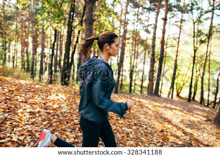 runner caucasian woman wearing dark gray jacket jogging in autumn park, right side view - stock photo