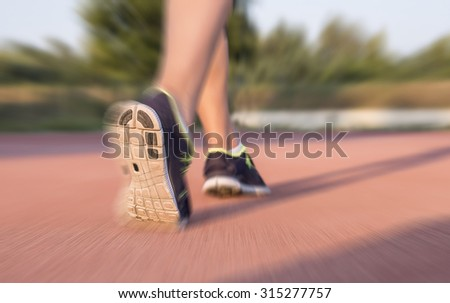 Runner feet running on athletic track, motion blur effect