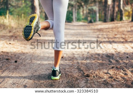 Runner feet running on road close-up on shoe. woman fitness at sunrise