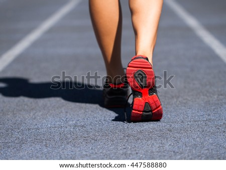 Runner feet running on road closeup on shoe at stadium. Woman fitness jog workout welness concept.