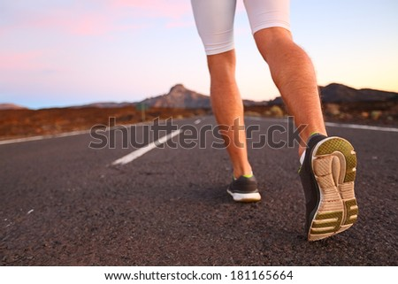 Runner feet running on road closeup on shoe. Man fitness athlete jogger workout in wellness concept at night. - stock photo
