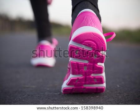 Runner feet running on road. Shoe close-up. - stock photo