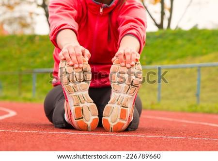 Runner feet running on running track closeup on shoe - stock photo