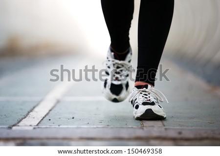 Runner feet walking on road closeup on shoe. woman fitness jog workout wellness concept. - stock photo