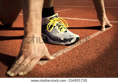 Runner in a stadium is in start position with hands on the line
