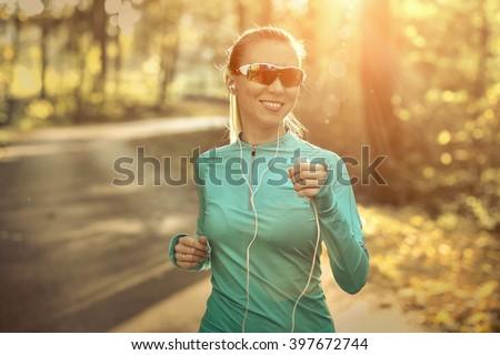 Runner in action at autumn under sunlight. - stock photo