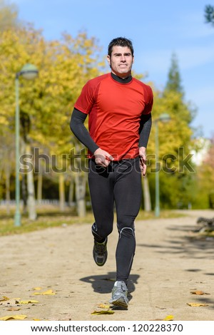 Runner in park. Handsome athlete jogging outdoors on autumn. - stock photo