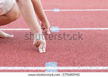 runner is in start position with hands on the line in track running - stock photo