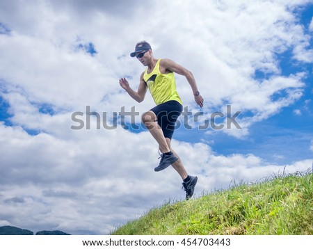 Runner jumping from hill. Training in mountains.